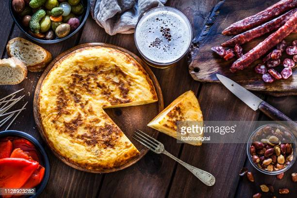 tapas: spanish tortilla, chorizo, pimientos, olives and beer shot from above - prepared potato stock pictures, royalty-free photos & images