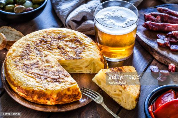 tapas: spanish tortilla, chorizo, pimientos, olives and beer shot from above - olive pimento stock photos and pictures