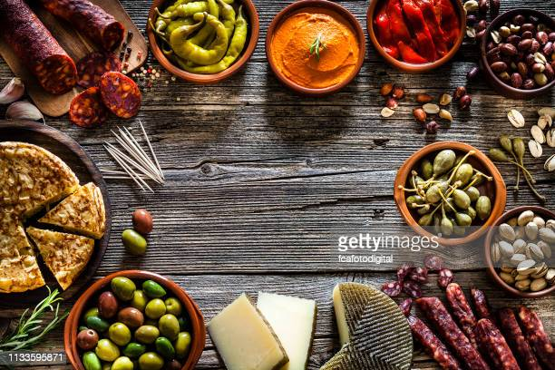 tapas: typical spanish food shot from above making a frame - olive pimento stock photos and pictures