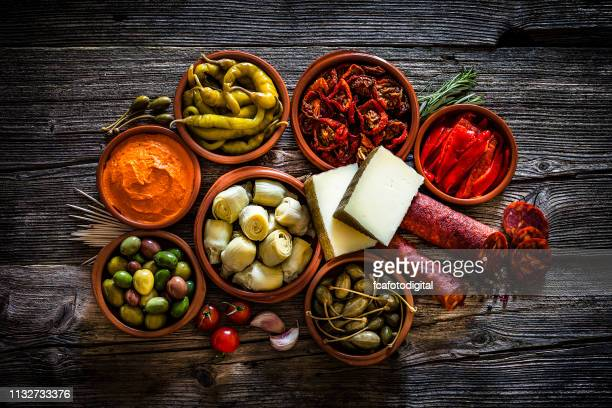 tapas: typical spanish food shot from above on rustic wooden table - tapas stock photos and pictures