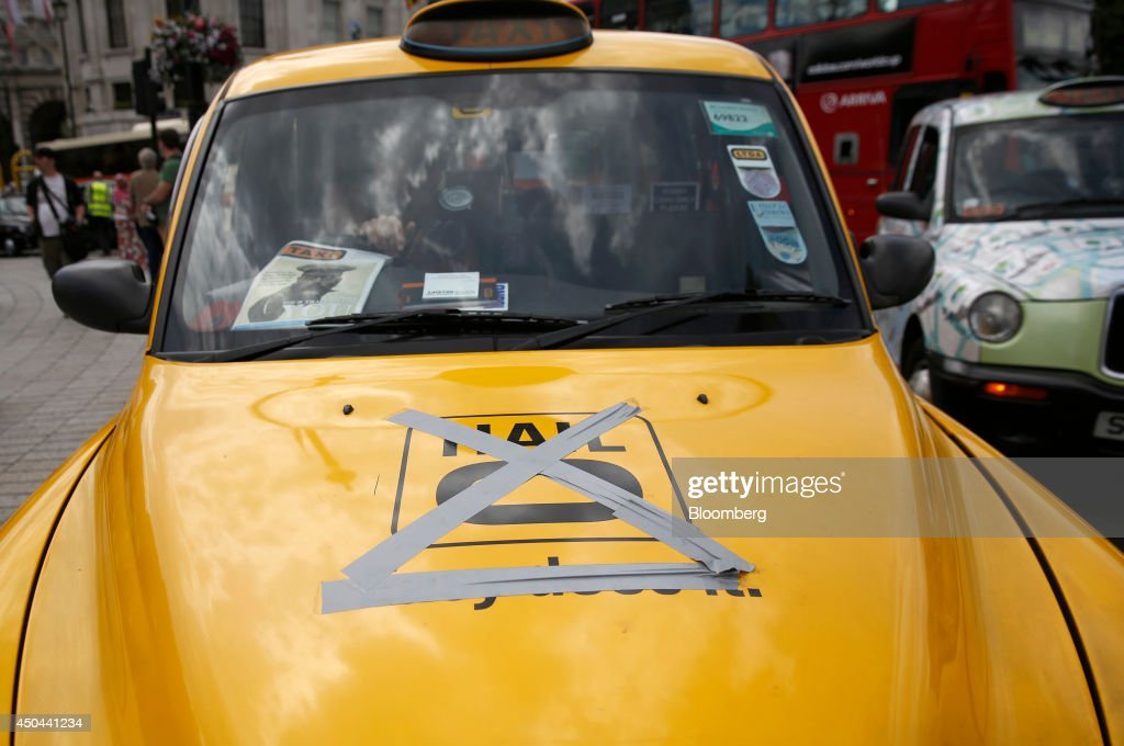 Tape covers a Hailo logo on the hood of a yellow London taxi cab parked on Trafalgar Square, during a protest against Uber Technologies Inc.'s car sharing service in London, U.K., on Wednesday, June 11, 2014. Traffic snarled in parts of Madrid and Paris today, with a total of more than 30,000 taxi and limo drivers from London to Berlin blocking tourist centers and shopping districts. Photographer: Simon Dawson/Bloomberg via Getty Images