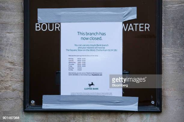 Tape holds a sign informing customers of a closure of a Lloyds Banking Group Plc bank branch in Bourton-on-the-Water near Cheltenham, U.K., on...