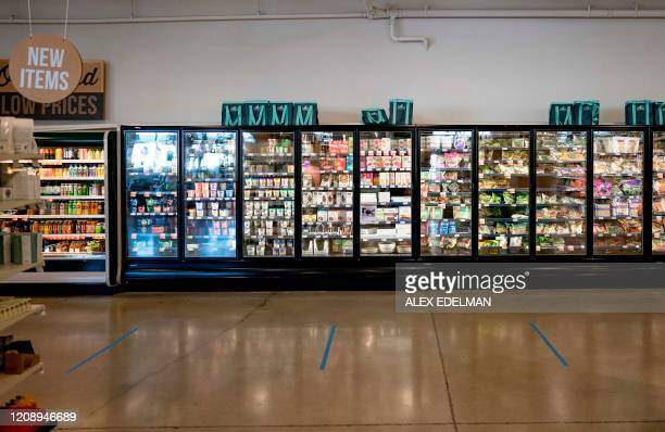 Tape marking safe social distancing positions in the check out line at a MOM's Organic Market on April 2 2020 in Washington DC
