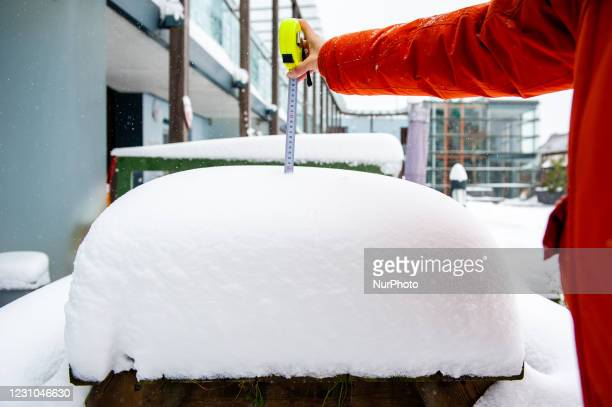 Tape measure is showing the centimeters of snow accumulated over a wood bench, during the snowstorm Darcy in Nijmegen, on February 8th, 2021.