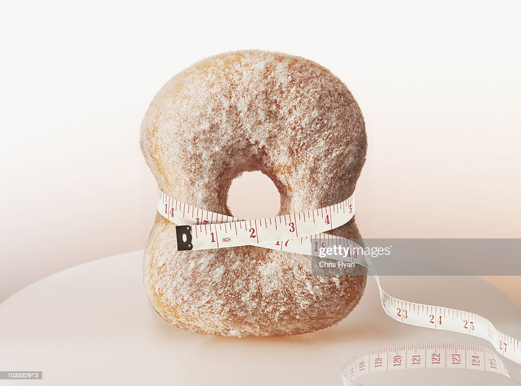 Tape measure squeezing donut : Stock Photo