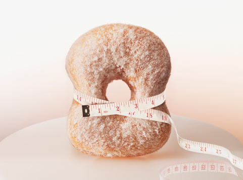 Tape measure squeezing donut - gettyimageskorea