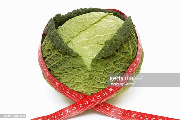 Tape measure wrapped around savoy cabbage, close-up