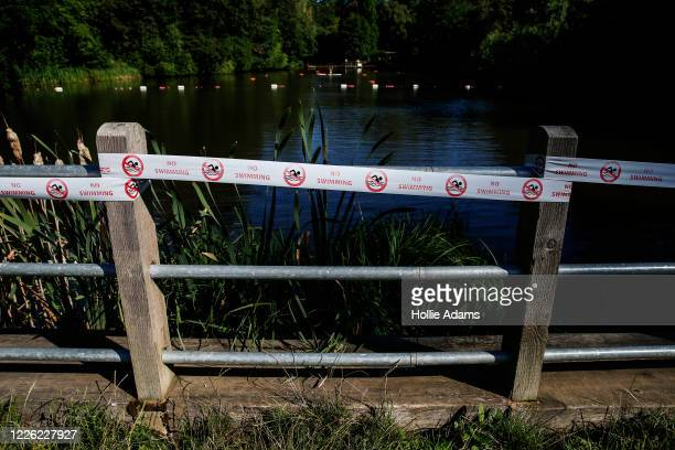 Tape showing 'no swimming' signs still adorns the fence as Hampstead Heath's mixed bathing pond reopens to the public on July 11, 2020 in London,...