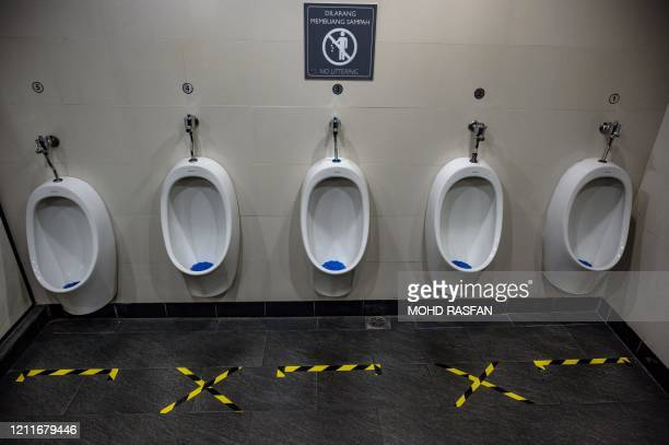 Tape to mark spaces for social distancing are seen on the floor in front of urinals at a toilet in Kuala Lumpur on May 4 as Malaysia eases its...