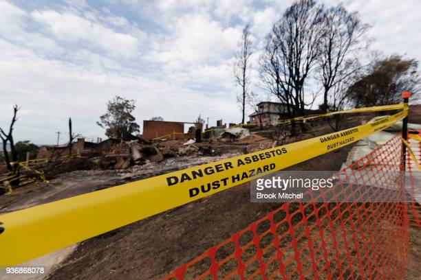 Tape warning of the dangers of asbestos in the air around older homes destroyed by fire in Tathra Australia on March 23 2018 A bushfire which started...