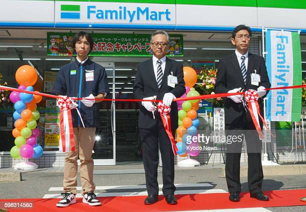 A tapecutting ceremony is held at a FamilyMart convenience store in Nagoya central Japan on Sept 1 to celebrate the merger of FamilyMart Co and Uny...