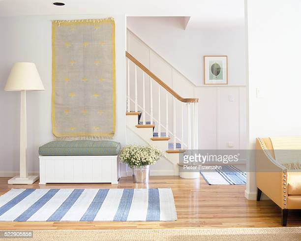 Tapestry and striped rugs in colorful entryway