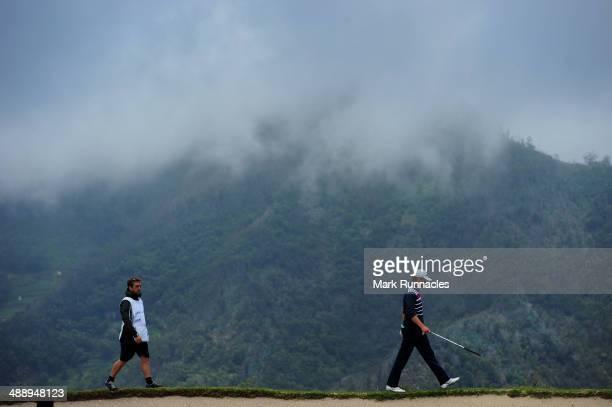Tapio Pulkkanen of Finland walks along a ridge line after over shooting the 4th green during the Madeira Islands Open Portugal BPI at Club de Golf do...