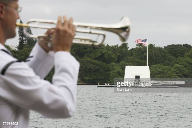 Taps is played with the USS Memorial in the background during the 65th Anniversary of Pearl Harbor Day Commemoration ceremonies December 7 2006 in...