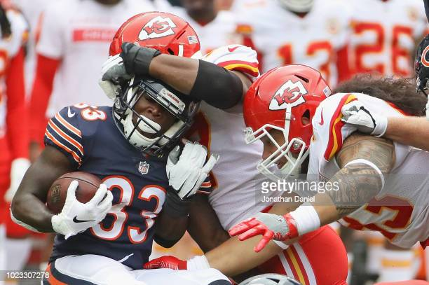 Taquan Mizzell of the Chicago Bears is stopped by Breeland Speaks and Mike Purcell of the Kansas City Chiefs during a preseason game at Soldier Field...