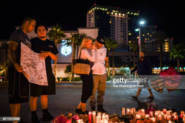 Tara Boze center wipes a tear at a street vigil with Steven Vasquez that was held for the victims along the Las Vegas Strip a day after 59 people...