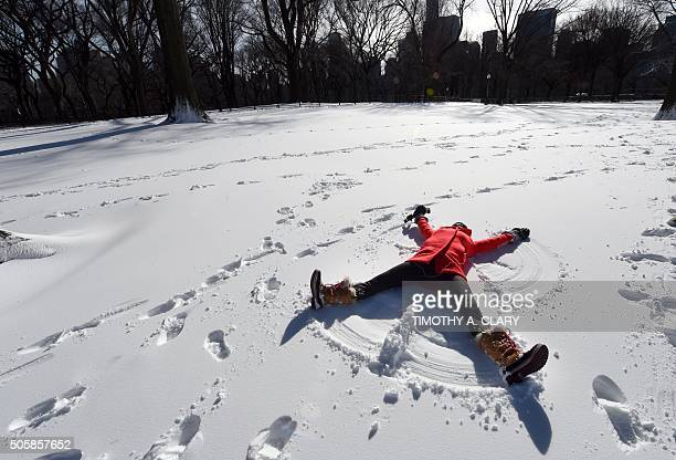 Tara Jakeway with Chasing News makes a snow angel in the manmade snow in Central Park January 20 2016 as part of Winter Jam NYC's Ultimate Snow Day...