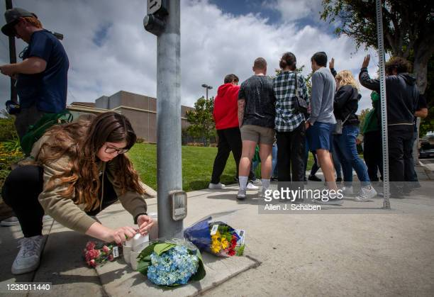 Tara Seifert who worked at Starbucks Wednesday night with Aden, lights a candle placed next to flowers as fellow Starbucks employees and friends...