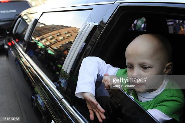 Tara Uselding of Highlands Ranch wave from a MakeAWish limousine while riding with her family during the St Patrick's Day Parade Saturday March 12 in...