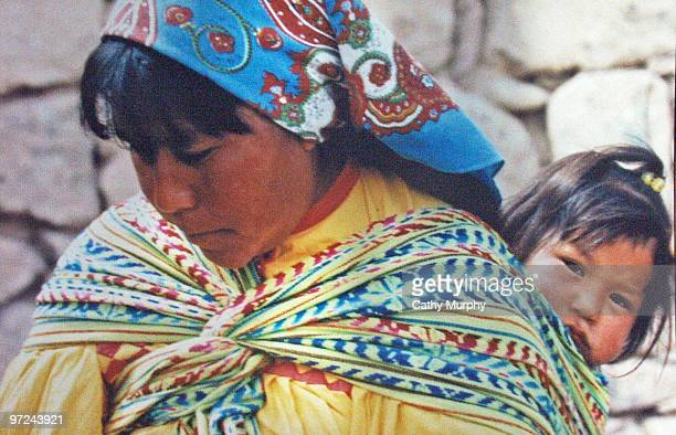 Tarahumara baby, carried on her mother's back, peeks around her shoulder, near Copper Canyon, outside of Creel, Mexico, ca.2000.