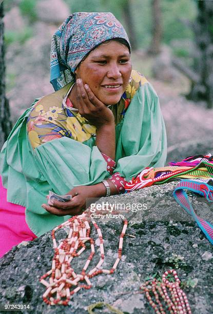 Tarahumara woman sells her wares, consisting of beaded jewelry and woven belts, Copper Canyon, Mexico, 1998.