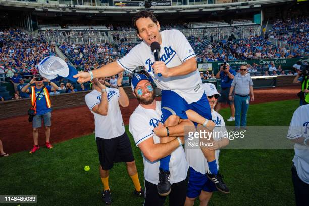 Taran Killam and Kevin Pollak hoist Paul Rudd up after playing in the celebrity softball game at Kauffman Stadium during the Big Slick Celebrity...