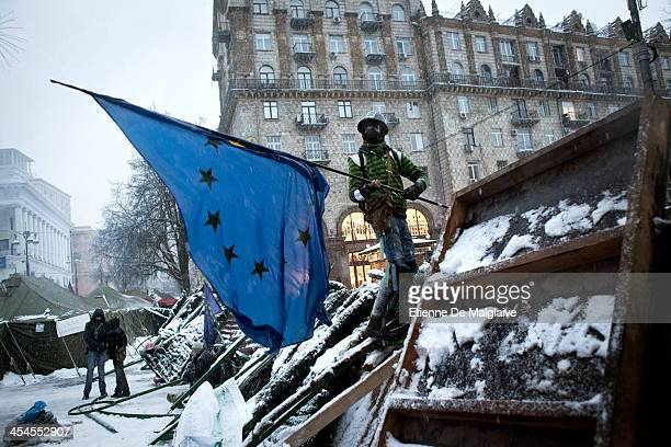 Taras an antigovernment protester stand guard and raises an European flag a symbol of the protest movment at one of the barricades defending Maidan...