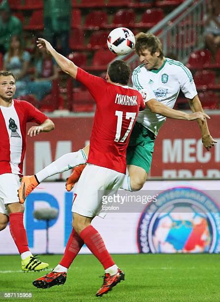 Taras Mykhalyk of FC Lokomotiv Moscow challenged by Oleksandr Kasyan of FC Tom Tomsk during the Russian Premier League match between FC Lokomotiv...