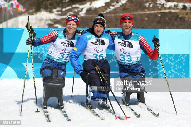 Taras Rad of Ukraine celebrates victory in the Men's Biathlon 125km Sitting with Silver medallist Daniel Cnossen of USA and Bronze medallist Andrew...