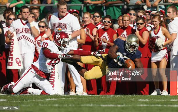Tarean Folston of the Notre Dame Fighting Irish is knocked out of bounds just short of the goal by Quentin Hayes of the Oklahoma Sooners at Notre...