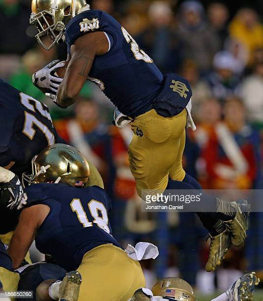 Tarean Folston of the Notre Dame Fighting Irish leaps to score the winning touchdown against the Navy Midshipmen at Notre Dame Stadium on November 2...