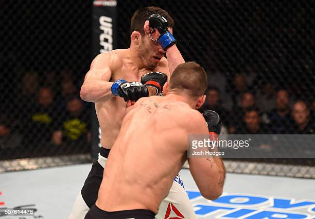 Tarec Saffiedine punches Jake Ellenberger in their welterweight bout during the UFC Fight Night event at the Prudential Center on January 30, 2016 in...