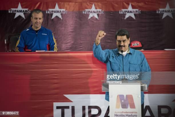 Tareck El Aissami Venezuela's vice president left smiles as Nicolas Maduro Venezuela's president raises a fist during a Tupamaro political party...