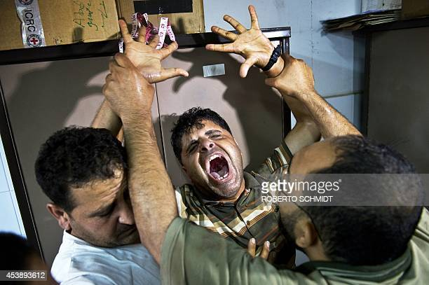 Tarek alRifi the father of one of the three children from the AlRifi family killed in an Israeli military strike reacts at Gaza city's AlShifa...