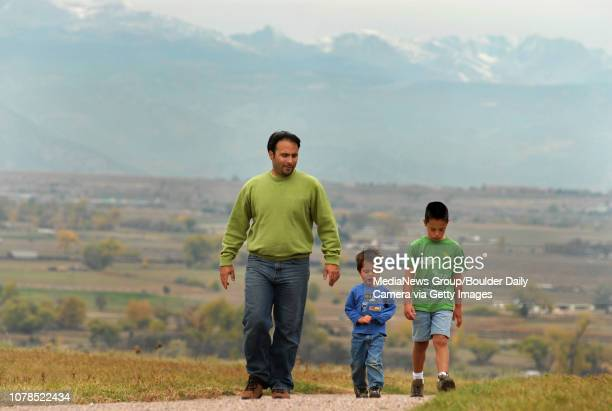 Tarek Dimachkie left walks with his sons Nolan and Aiden along the open space by Ridgeview Heights neighborhood on Saturday