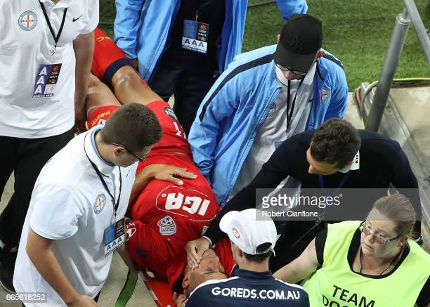 Tarek Elrich of United is comforted by United Head Coach Guillermo Amor as he is stretchered off with an injury during the round 26 ALeague match...