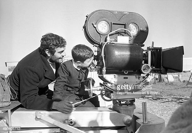 Tarek Sharif looking through a camera in front of his father and Egyptian actor Omar Sharif on the set of of the film Doctor Zhivago 1965