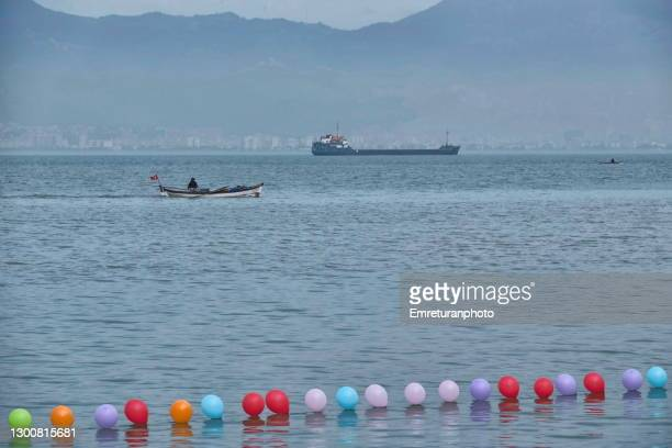 target baloons and fishing boat and anchored ship at the background. - emreturanphoto stock-fotos und bilder