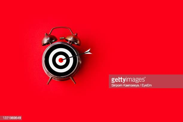 target time, goal sign on clock face over red background with copy space - aiming stock pictures, royalty-free photos & images