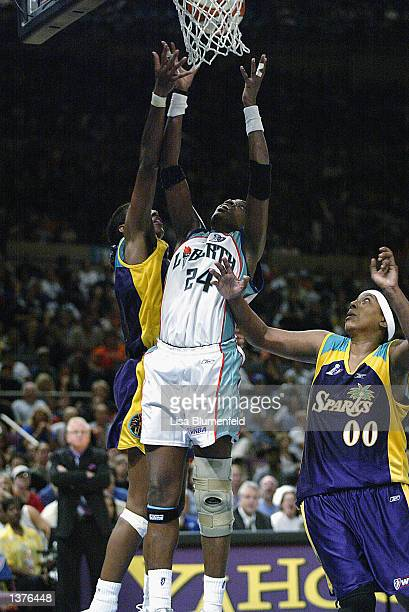 Tari Phillips of the New York Liberty jumps for a rebound with Lisa Leslie of the Los Angeles Sparks in game one of the 2002 WNBA Finals on August 29...
