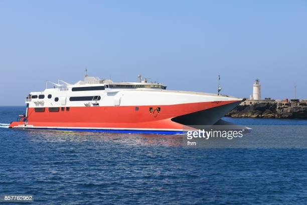 tarifa lighthouse and an arriving speed ferry from africa (cadiz province/ andalusia/ spain) - ferry stock pictures, royalty-free photos & images