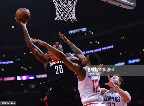 Tarik Black of the Houston Rockets attempts a layup on Tyrone Wallace and Blake Griffin of the LA Clippers during the first half at Staples Center on...