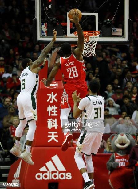 Tarik Black of the Houston Rockets goes up for a dunk in the second half defended by John Henson of the Milwaukee Bucks and Eric Bledsoe at Toyota...