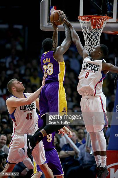 Tarik Black of the Los Angeles Lakers drives past Cole Aldrich and Jeff Green of the Los Angeles Clippers during an NBA game between Los Angeles...