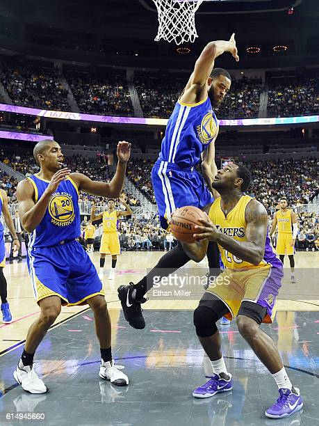 Tarik Black of the Los Angeles Lakers is fouled by JaVale McGee of the Golden State Warriors as James Michael McAdoo of the Warriors defends during...