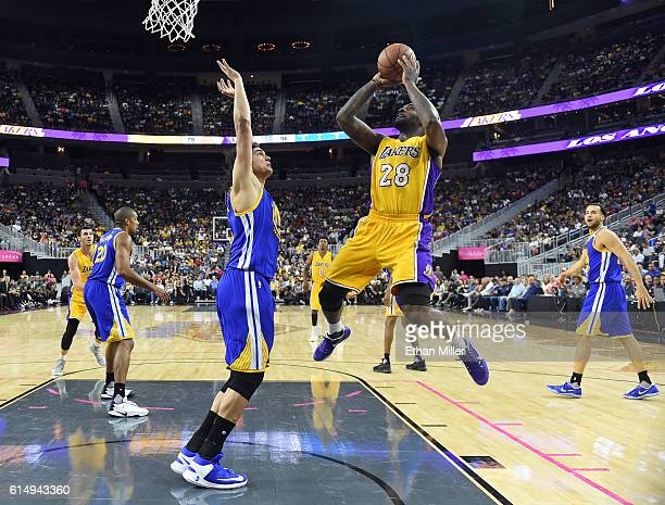 Tarik Black of the Los Angeles Lakers shoots against Anderson Varejao of the Golden State Warriors during their preseason game at TMobile Arena on...