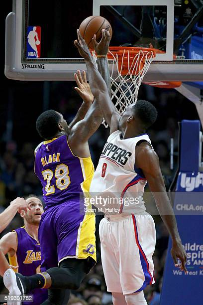 Tarik Black of the Los Angeles Lakers shoots past Jeff Green of the Los Angeles Clippers during the second half of an NBA game against the Los...