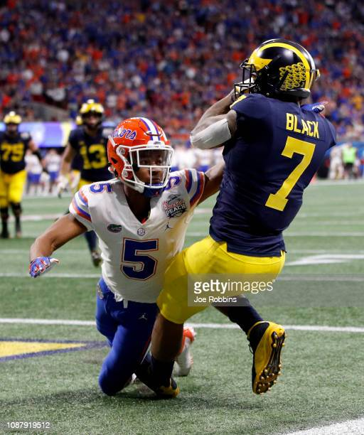 Tarik Black of the Michigan Wolverines drops a pass under pressure from CJ Henderson of the Florida Gators in the fourth quarter during the ChickfilA...