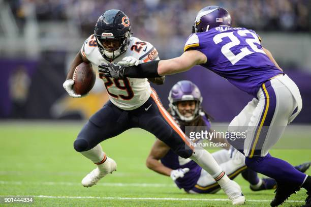 Tarik Cohen of the Chicago Bears carries the ball against Trae Waynes and Harrison Smith of the Minnesota Vikings during the game on December 31 2017...