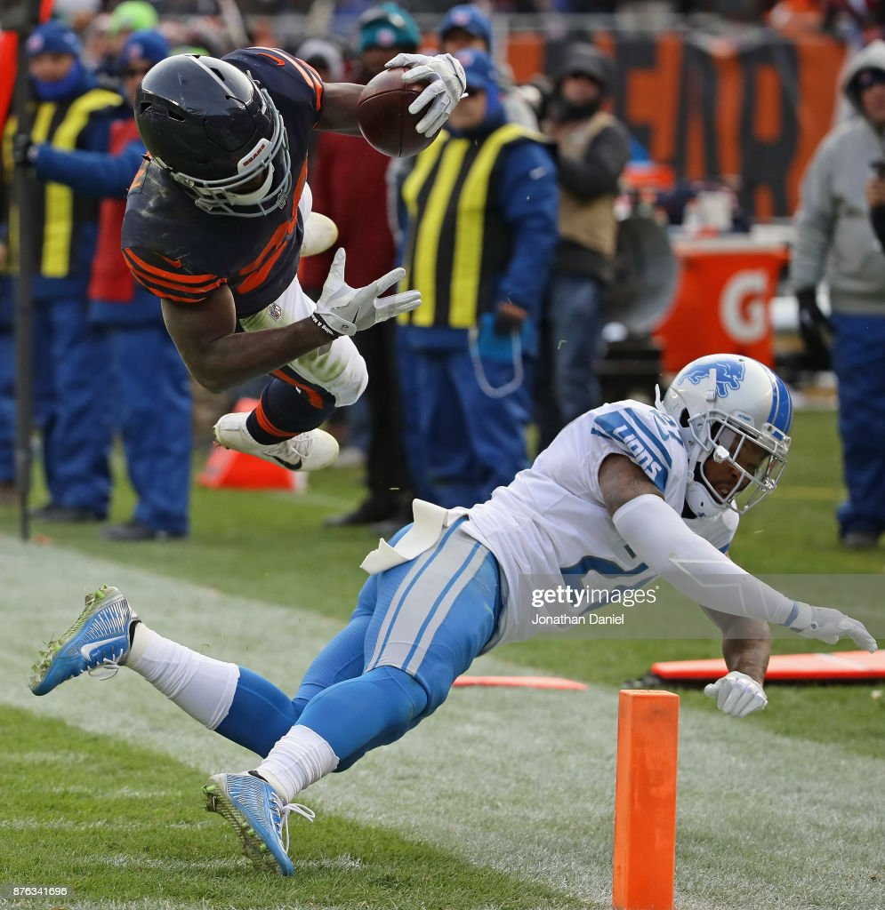 Tarik Cohen #29 of the Chicago Bears is hit by Glover Quin #27 of the Detroit Lions as he runs to the end zone at Soldier Field on November 19, 2017 in Chicago, Illinois. The Lions defeated the Bears 27-24.